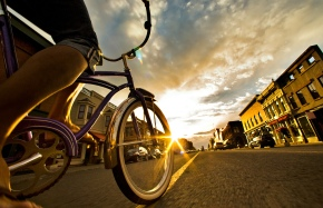 A woman riding a bike at sunset through a town.